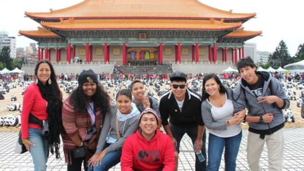 """UNITY youth leaders and their chaperones pose in front of Taiwan's National Concert Hall. The National Theater and Concert Hall are two of the first major modern performing arts facilities to be established in Asia. On this day a large ceramic panda exhibit was on display. Pictured, from left in the back, are Mary Kim Titla, Carrie Hood, Tyler Owens, Aaron Leaureaux, Santana """"Sonny"""" Johnson, Christine Porter, and Simon Montelongo. Alex Toledo is in the front."""