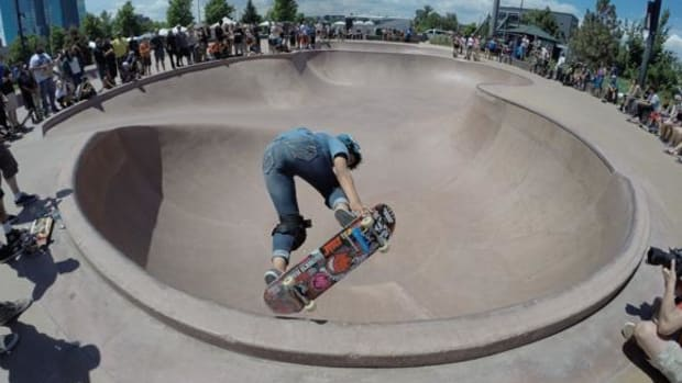 Lakota skater Emily Earring, 14, from Rapid City, South Dakota, grabs her board in a trick performed during her run in a skateboard competition hosted by the Stronghold Society in Denver.