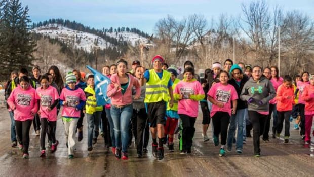 Runners go through the streets of Lame Deer, Montana side-by-side.
