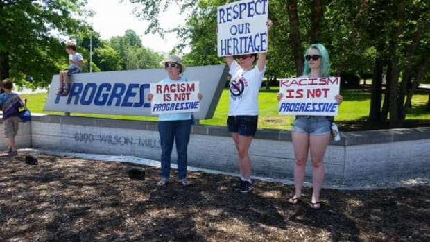 From left, Sue Collyer, Bee Schrull, Rachael Collyer protest outside of Progressive Insurance headquarters in Mayfield, Ohio.