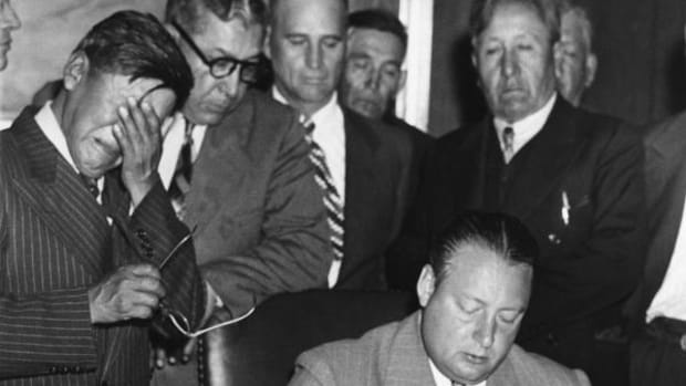"George Gillette, chairman of the Fort Berthold Indian Tribal Council weeps as he watches Secretary of the Interior A.J. King sign away the tribe's rights to the Missouri River and the loss of 700 miles of the most fertile of tribal lands on May 20, 1948. Krug is signing a contract that turned over 155,000 of the reservation in North Dakota for the Garrison Dam and Reservoir project. In a prepared statement, Gillete said: ""The members of the Tribal Council sign this contract with heavy hearts. Right now the future does not look good to us."""