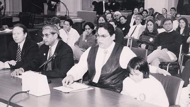 This black and white photo from the late 1990's shows Ernie Stevens Jr. with his then 11-year-old daughter Lois, testifying on mascots and racism in sports. Today, Lois is currently finishing her Master's degree at the University of Kansas.