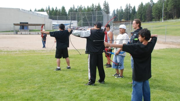 Taking time to keep and teach traditional skills is important to the Spokane tribe. (L to R) Anthony Salinas, Robert Seyler and Billy Salinas take careful aim.
