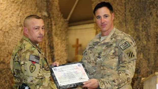 First Sgt. Lester Day, left, receives a certificate of appreciation from Master Sgt. Christopher Painter for his effort as the key note speaker at the Regional Command-South's National Native American Heritage Month Observance at Kandahar Airfield, Afghanistan, Nov. 23.  (DOD courtesy photo)