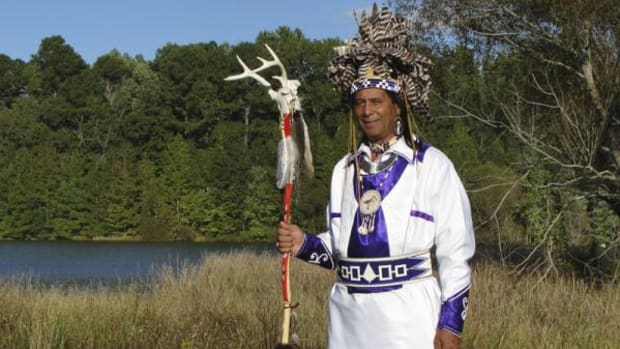 Principal Chief Wayne Mackanear Brown on Meherrin tribal land. The three figures at the lower edge of the chief's regalia represent the Tuscarora, Meherrin, and Nottoway peoples—nations of the Southern Iroquois Confederacy.