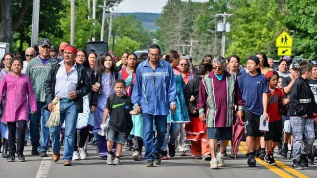 Onondaga Nation leader Tadodaho (Sid Hill), center, leads a walkout from the school on June 16. Only five students are left out of 130.