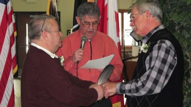 Tim LaCroix, left, puts Gene Barfield's wedding ring on his finger during the marriage ceremony performed by Little Traverse Bay Band Tribal Chairman Dexter McNamara. The ceremony was the first one following the tribe's passing of the Waganakising Odawak Marriage Statute legally recognizing same-sex marriage on the reservation.