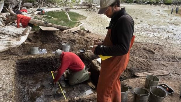 On Calvert Island, archaeologist Daryl Fedje takes a measurement in a mucky pit while colleague Duncan McLaren records the data.