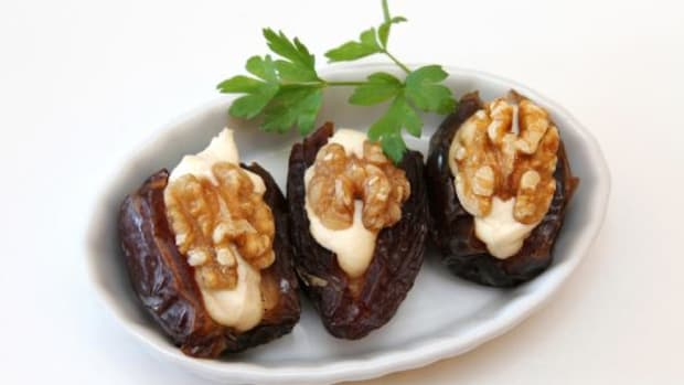 There are many ways to stuff a date. One of the easiest is using goat or cream cheese and topping it with a walnut.