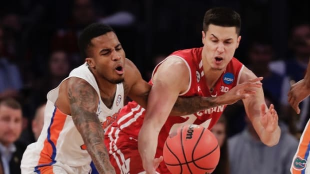 Florida forward Justin Leon, left, and Wisconsin guard Bronson Koenig (24) scramble for a loose ball in the second half of an East Regional semifinal game of the NCAA men's college basketball tournament, Saturday, March 25, 2017, in New York. (AP Photo/Julio Cortez)