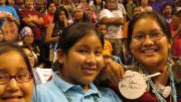 Megan LaRose, 16, Navajo, seated with family members, shows off her beaded medallion signed by Shoni Schimmel.