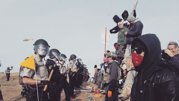 A line of prayers and police facing off at construction site of the Dakota Access Pipeline. The takeaway: Stay peaceful, and stand firm.