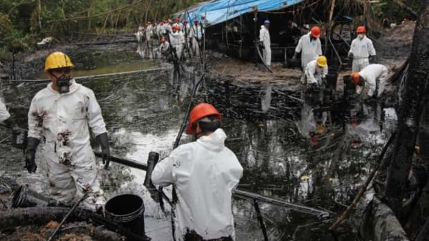 Workers, many hired from local villages, clean up some of the 2,000 to 3,000 barrels of oil spilled from a ruptured pipeline in Awajún territory in northern Peru.