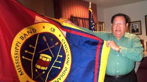 Chief Phillip Martin of the Mississippi Band of Choctaw Indians poses with the Choctaw flag in his office in 2002 on the tribal reservation.