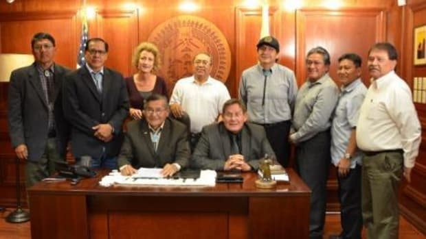 From left, Council Delegate Walter Phelps, Council Delegate Lorenzo Curley, Deputy Attorney General Dana Bobroff, President Ben Shelly (sitting), Council Delegate Roscoe Smith, Speaker Pro Tem LoRenzo Bates (sitting), Council Delegate Jonathan Nez, Attorney General Harrison Tsosie, Navajo Tax Commission director Martin Ashley, and OPVP Chief of Staff Arbin Mitchell.