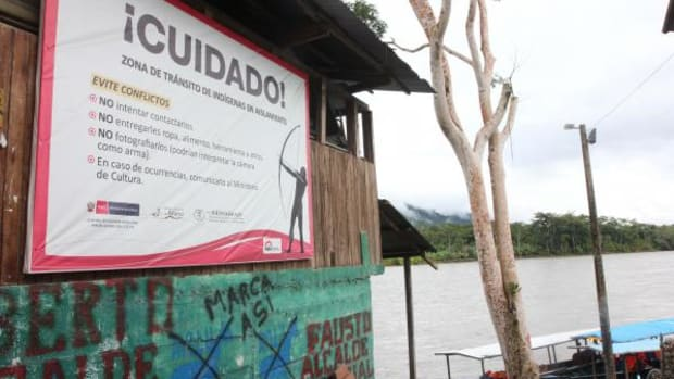 This sign, outside the Ministry of Culture in the port on the Madre de Dios River, cautions that if travelers see nomadic people along the riverbanks, they should not try to contact them; give them clothing, food or other items; or take photos (in case cameras are interpreted as weapons), and to inform the Ministry of Culture of any sightings or encounters.