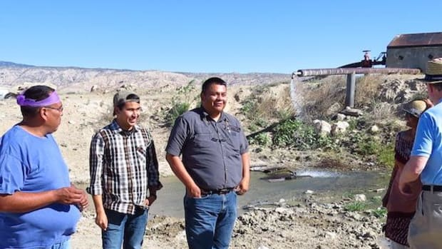 The well site shortly after a prayer was performed by medicine man Emery Begay (left). Kevin Felix (center), NTEC intern, stands with Sam Woods (right), NTEC business development manager at the hot springs well east of Tohatchi, N.M.