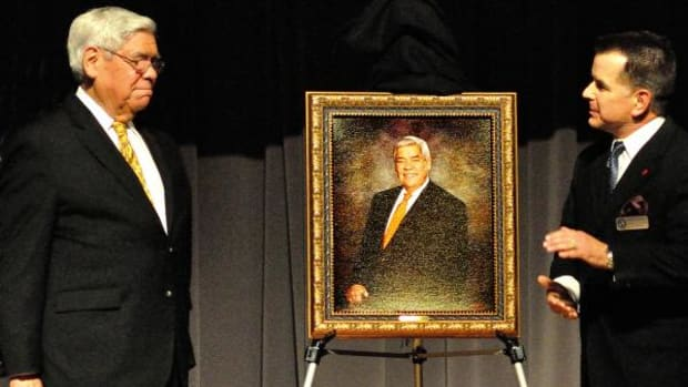 Neal McCaleb, left, Chickasaw Nation Ambassador At-Large to the United States, receives applause at the unveiling of his portrait in a ceremony honoring him by the Putnam City Public Schools Foundation. Joining the ambassador on stage is the foundation's chairman, Charles Lundeen.