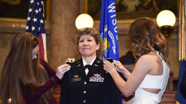 The daughters of Brigadier General Joane Mathews pin her new rank on her shoulders.