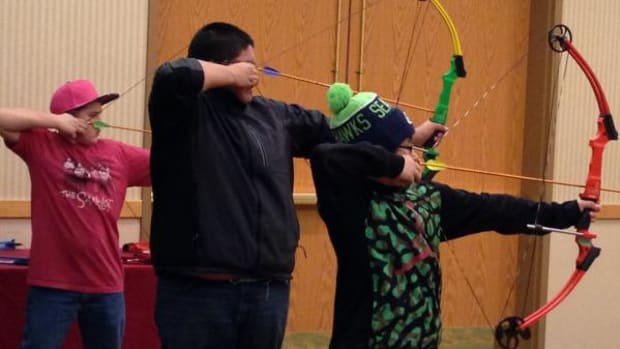 Cheyenne Eagle Butte Elementary School archers draw their bows at an archery competition. An all-Lakota youth archery team from South Dakota is on its way to a national tournament.