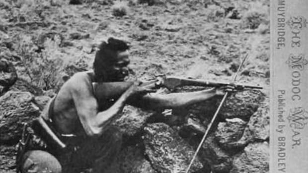 """Seeking an image of a Modoc fighter and figuring that one Native looked pretty much like any other, Muybridge posed Warm Springs scout Loa-kum Ar-nuk. The photographer put the scout down sighting a Spencer carbine steadied by a shooting stick. This image from the right emphasizes Loa-kum Ar-nuk's low stance behind a rock wall and his thousand-yard stare. Transformed into a woodcut, this second image of the scout was published in the June 21, 1873, Harper's Weekly over the caption """"Modoc brave lying in wait for a shot."""""""