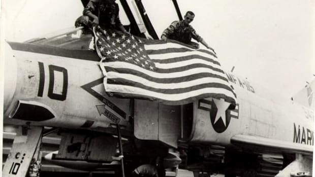 Ed McGaa and his co-pilot stretch the United States flag across the cabin of their fighter jet during the Vietnam War.