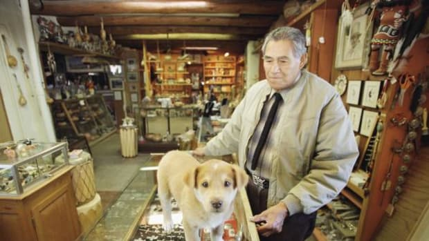 In this AP file photo from 1997: Tony Reyna, then 81, operates a modest shop selling Indian-made art from his hand-built adobe home in Taos, New Mexico. Reyna, who was twice governor of the pueblo on the town's north edge, has seen first-hand the struggle between tradition and growth within the Pueblo.