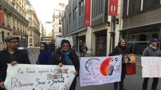 Protesters marched outside the site of an auction of sacred Hopi and other tribal artifacts in Paris that took place on December 7.
