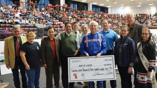 Shawn Slaton, CEO of Cherokee Nation Businesses, presents Cherokee Nation with a check for Heart of a Nation proceeds.
