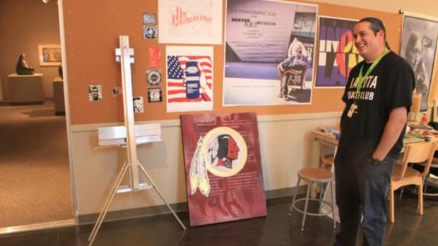 Gregg Deal, Pyramid Lake Paiute, is the Denver Art Museum's Native Arts Artist-in-Residence through January 31. Above, Deal stands before a painting of the logo of the Washington football team. Deal said he pricked himself with a needle to add blood to the painting.