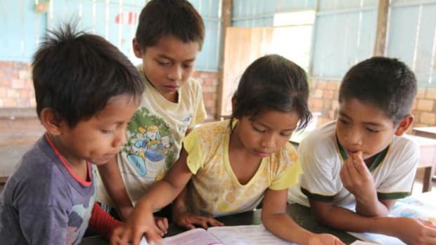 Young students share a book in a poorly equipped school along the Urituyacu River, in a remote part of the northeastern Peruvian Amazon.