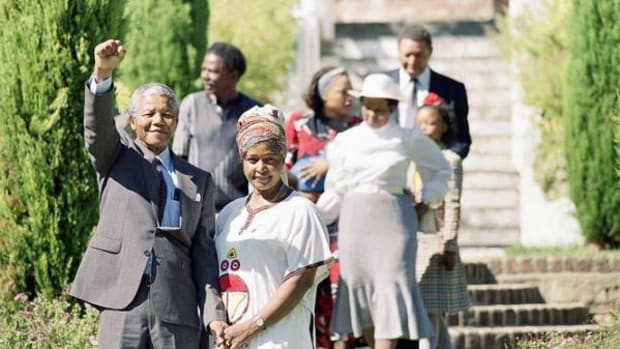 A smiling Nelson Mandela, released African National Congress leader, gives a black power salute at Archbishop Desmond Tutu's residence in Cape Town, South Africa, February 12, 1990. Mandela was freed from prison after serving over 27 years. At right is his wife Winnie Mandela.