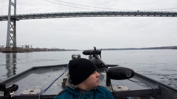 Darryl Lazare Jr. goes fishing with his grandfather on the Saint Lawrence River, the same water his grandfather fished on with his father. A bridge connecting the U.S. and Canada looms in the background.