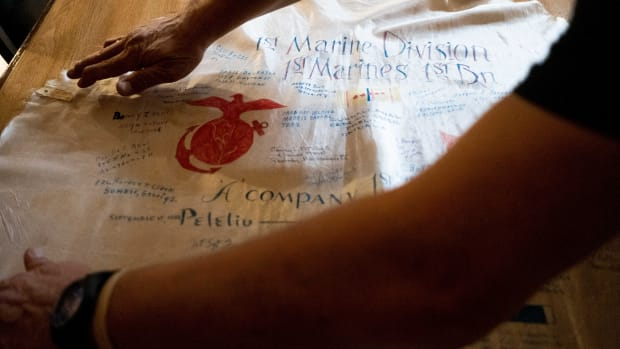 U.S. Army veteran Dwight Bero Sr. lays-out a piece of parachute from Post 1479's shadowbox. The cloth is adorned with the signatures of U.S. Marines that fought in Peleliu and Okinawa during World War II.