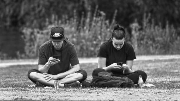 Pictured: A man and woman using cell phones.