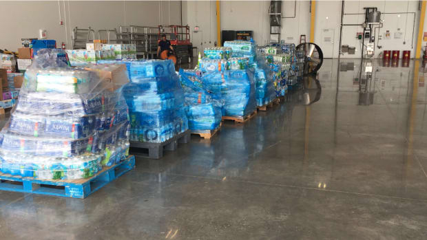 Cases of water collected by the Seminole Tribe stack up in the warehouse awaiting shipment to the Bahamas. Once taken by plane, the tribe is shifting to delivering by sea due to tropical storm warnings.