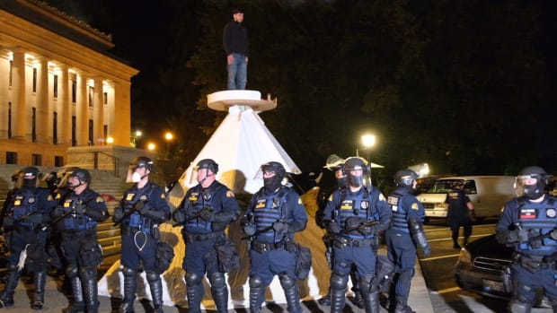 Washington State Patrol officers in riot gear prepare to remove a tarpee and the sitter on top of it from a prayer gathering at the capitol steps on September 25.