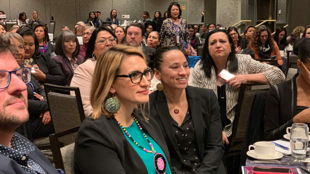 Lt. Gov. Peggy Flanagan and Rep. Sharice Davids listen to the speaker at the lunch.
