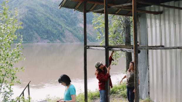 While waiting for fish nets to fill, women check out the racks used to dry salmon at their family's fish camp on the Yukon River in Alaska. (Photo by Meghan Sullivan, Indian Country Today)