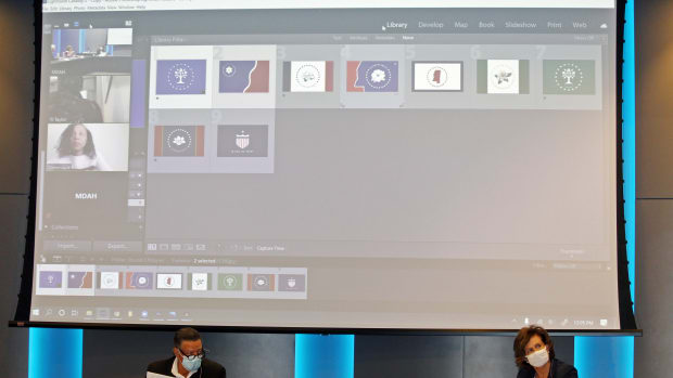 Reuben Anderson, seated left, and Mary Graham, and other members of a commission that will recommend a new Mississippi state flag, discuss flag choices on Friday, Aug. 14, 2020. The screen above Anderson and Graham shows people participating remotely in the commission meeting and images of nine flags chosen as finalists, although a graphic artist was set to make small changes to some of the designs. Mississippi recently retired the last state flag in the U.S. that included the Confederate battle emblem. (Photo by Emily Wagster Pettus, AP)