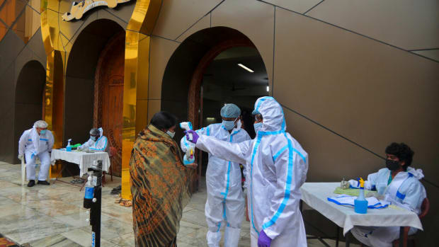 Baptist Church members wearing personal protective suits check the body temperature of devotees arriving to attend a Sunday service in Hyderabad, India, Sunday, Aug. 16, 2020. India is the third hardest-hit country by the pandemic in the world after the United States and Brazil. (AP Photo/Mahesh Kumar A.)