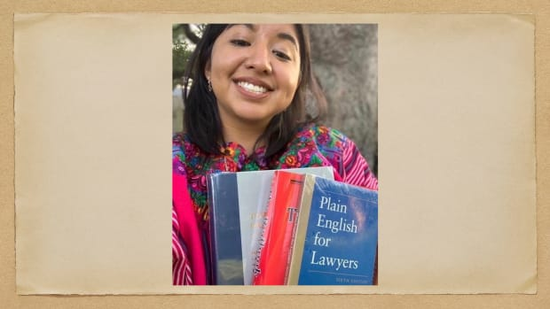 Alma Buena, a Pre-Law Online Seminar student, posing with the books that she was sent to participate in the 2020 program for American Indian and Alaska Native students. (Photo by Alma Buena)