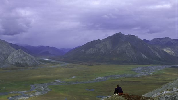 An unidentified person sits on rock above Arctic National Wildlife Refuge in this undated photo. An expected surge in lightning caused by climate change could mean increased wildfires for much of the Arctic. (Photo by U.S. Fish and Wildlife Service Headquarters/Steve Chase)