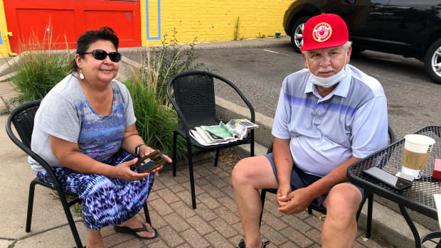 """MINNEAPOLIS, Minn. (July 15, 2020) -- Lisa Bellanger (left) and Frank Paro sit in front of the Pow Wow Grounds coffee shop on Franklin Avenue in Minneapolis. They were named co-chairs of the American Indian Movement's Grand Governing Council in May.  """"One of the things that has kept me in the movement is its spiritual roots,"""" said Bellanger. """"It's behind most of AIM's work over the years. Protecting Mother Earth."""""""