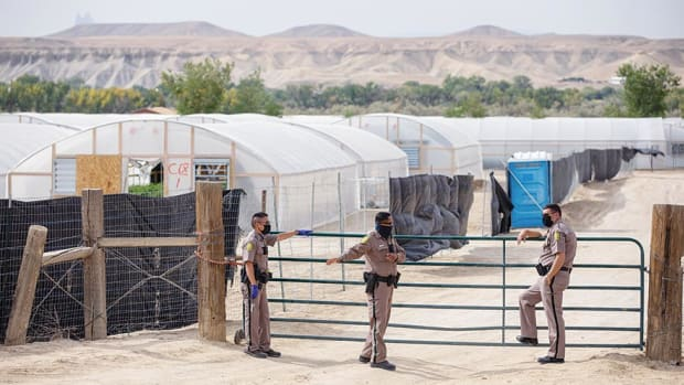 Navajo Nation Police stand outside one of Dineh Benally's hemp farms on Tuesday, Sept. 22, 2020. The police were implementing a restraining order against the farms. (Photo by Sharon Chischilly, Navajo Times)