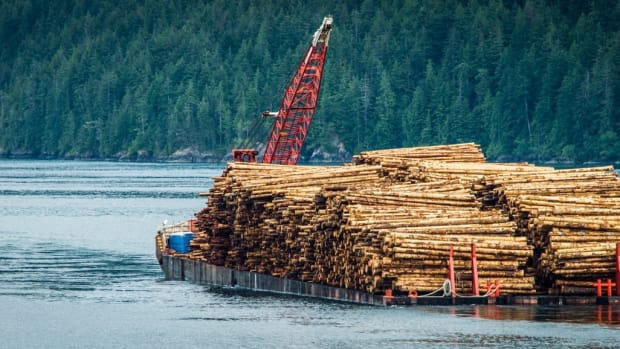 Raft of logs being towed by a barge. (Photo by Ted McGrath, courtesy of Creative Commons)