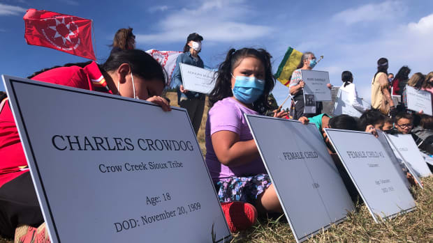 In this Monday, Oct. 12, 2020, photo, children with placards bearing the names of students who died at the old Rapid City Indian Boarding School sit in front of a hillside that researchers determined holds unmarked graves of some of the deceased children. A memorial is planned to honor the children at the site. (Photo by Stewart Huntington)