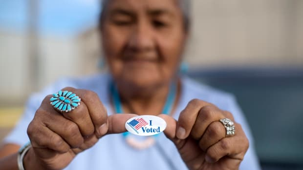 """FILE - In this Aug. 28, 2018 file photo, Mildred James of Sanders, Ariz., shows off her """"I Voted"""" sticker as she waits for results of the Navajo Nation presidential primary election to be revealed in Window Rock, Ariz. The Navajo Nation is suing Arizona counties over what it says were unequal opportunities for tribal members to correct signature deficiencies on early ballots in Arizona's general election. The tribe is asking a federal judge in a lawsuit filed this week to allow more than 100 Navajos to make the fixes. The request has the potential to delay the state's certification of ballots, scheduled for Dec. 3. (AP Photo/Cayla Nimmo, File)"""