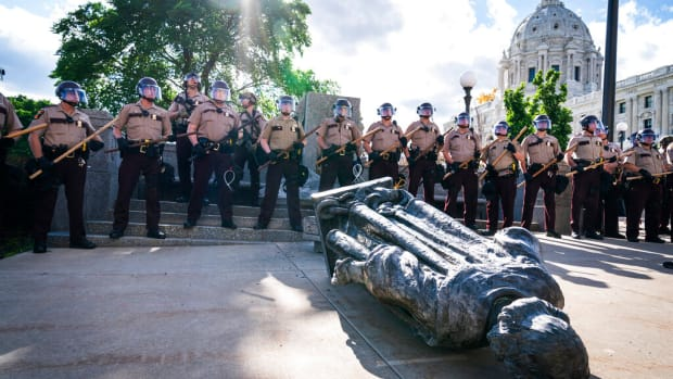 Minnesota State Troopers surrounded the statue of Christopher Columbus after it was toppled in front of the Minnesota State Capitol, Wednesday, June 10, 2020, in St. Paul, Minn. The statue was later towed away. (Leila Navidi/Star Tribune via AP)