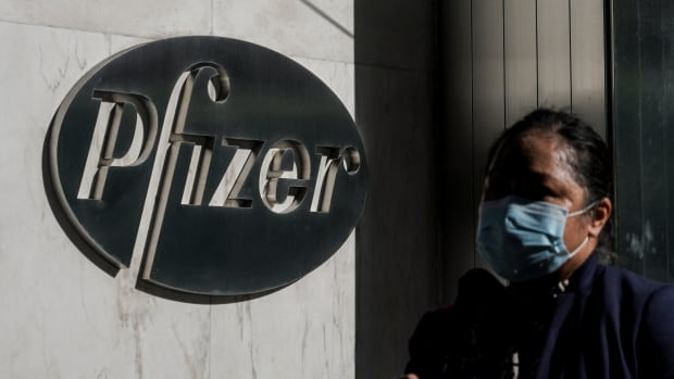 A pedestrian walk past Pfizer world headquarters, Monday Nov. 9, 2020, in New York. Pfizer says an early peek at its vaccine data suggests the shots may be 90% effective at preventing COVID-19, but it doesn't mean a vaccine is imminent. (AP Photo/Bebeto Matthews)